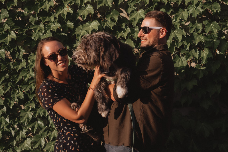 A couple wearing sunglasses laughs as they hold their dog together while standing against an ivy covered wall.