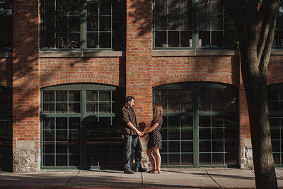 Couple holding hands and facing each other on a shady, sun dappled street lined with a brick building.