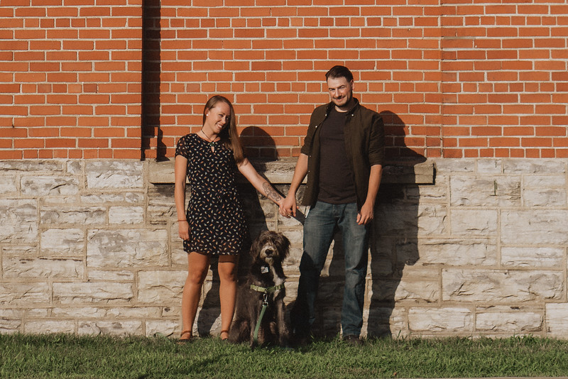 Couple smiling and holding hands against a brick wall in the bright, warm sun as their dog sits between them.