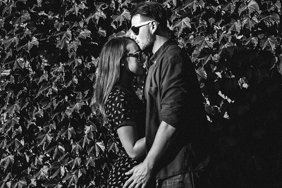 A man kisses his fiance's forehead. Both are wearing sunglasses, standing in front of an ivy covered wall.