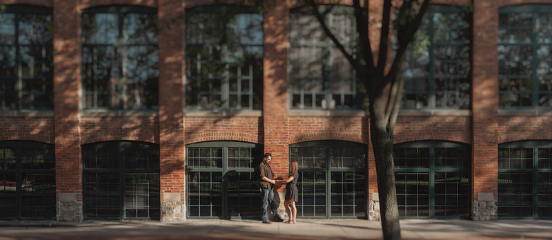 Couple holding hands on a shady, sun dappled street against a brick building.