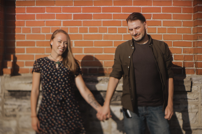 Couple smiling and holding hands in bright, warm sun against a brick wall.