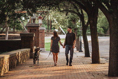 A couple looks at their dog as they walk her down a shady, tree lined, brick paved sidewalk. The dog is looking back up at the couple.