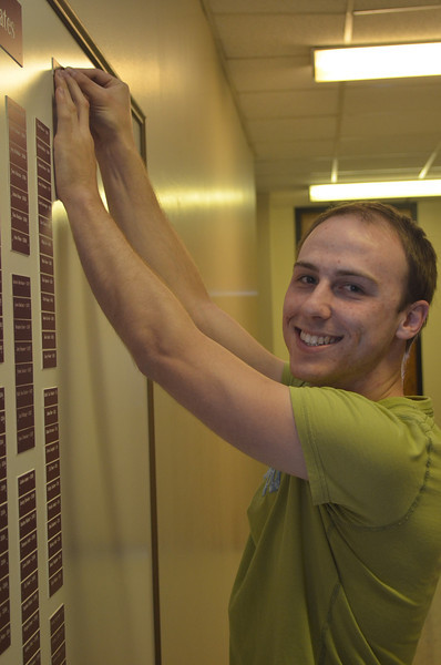 Adam Collins putting his nameplate on the Chemistry Graduates board.