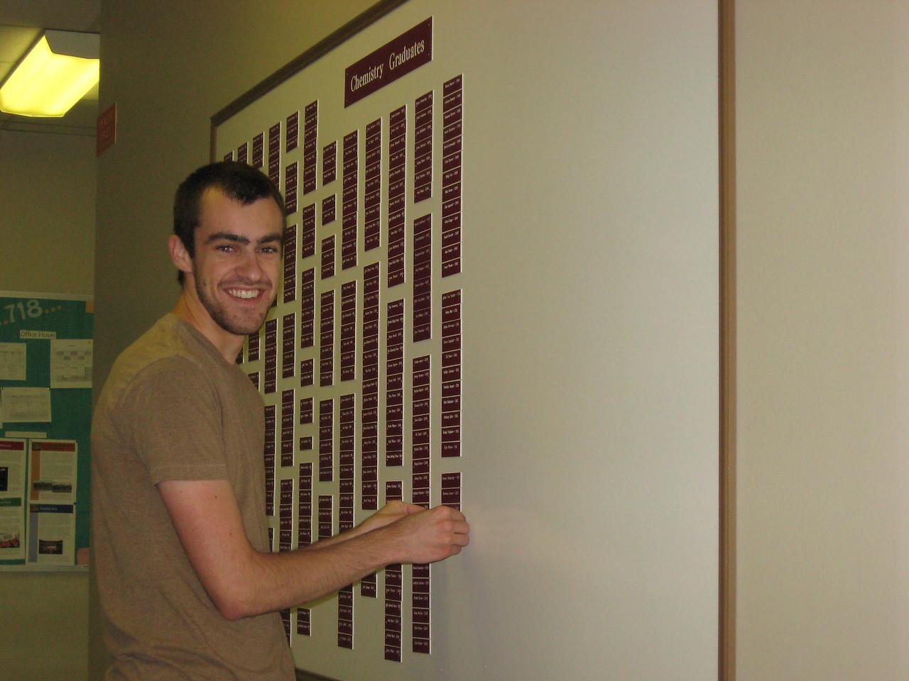 Jared Evatt putting hisr nameplate on the Chemistry Graduates board.