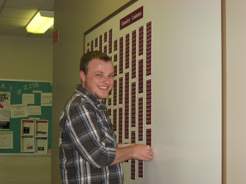 Spencer Whittenberg putting his nameplate on the Chemistry Graduates board.