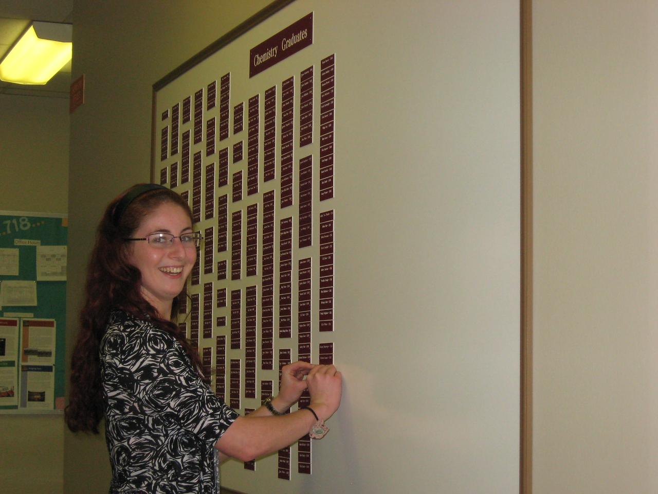 Michelle DuBois putting her nameplate on the Chemistry Graduates board.