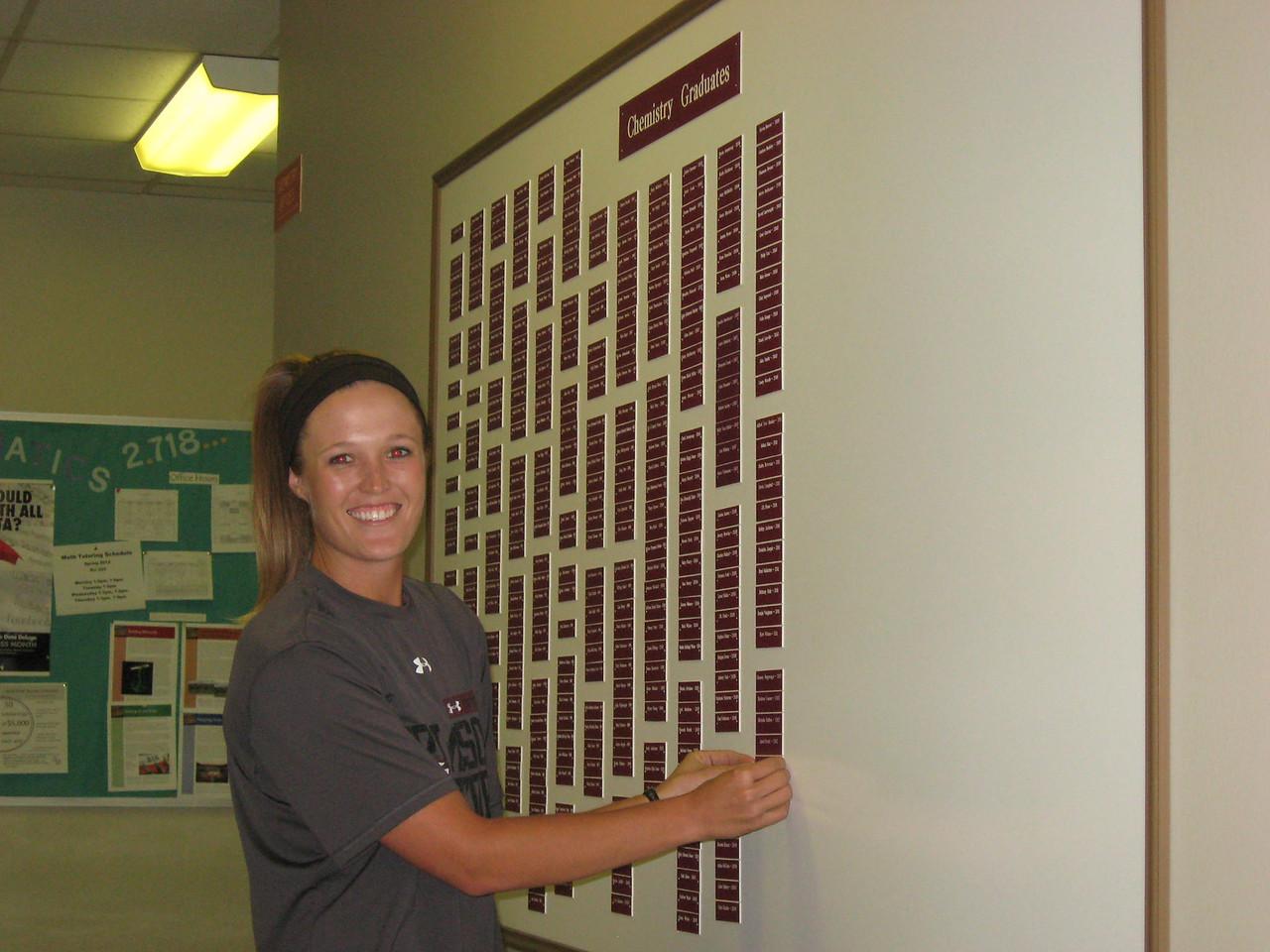Aubrey Jones putting her nameplate on the Chemistry Graduates board.