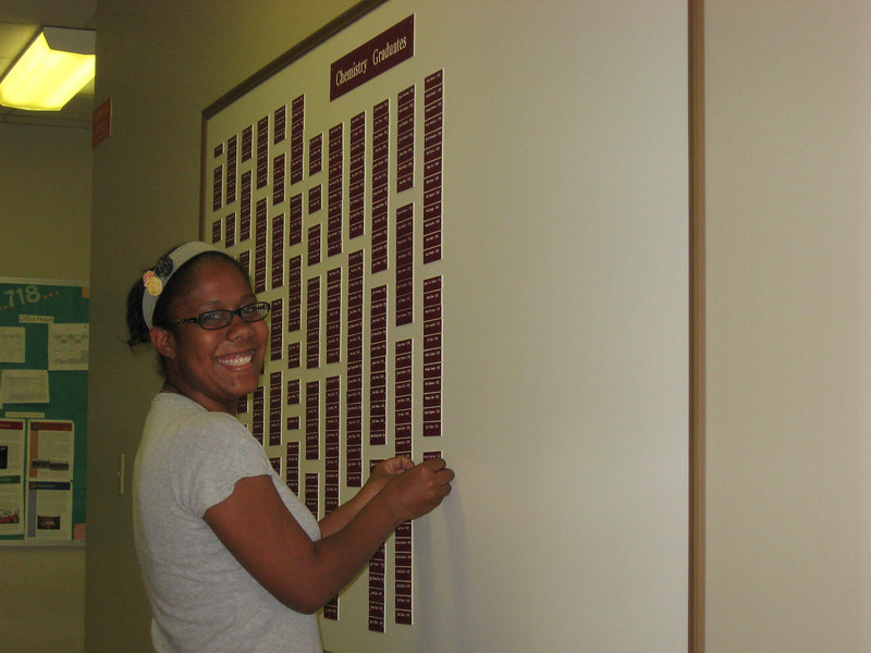 Kristeen Conner putting her nameplate on the Chemistry Graduates board.