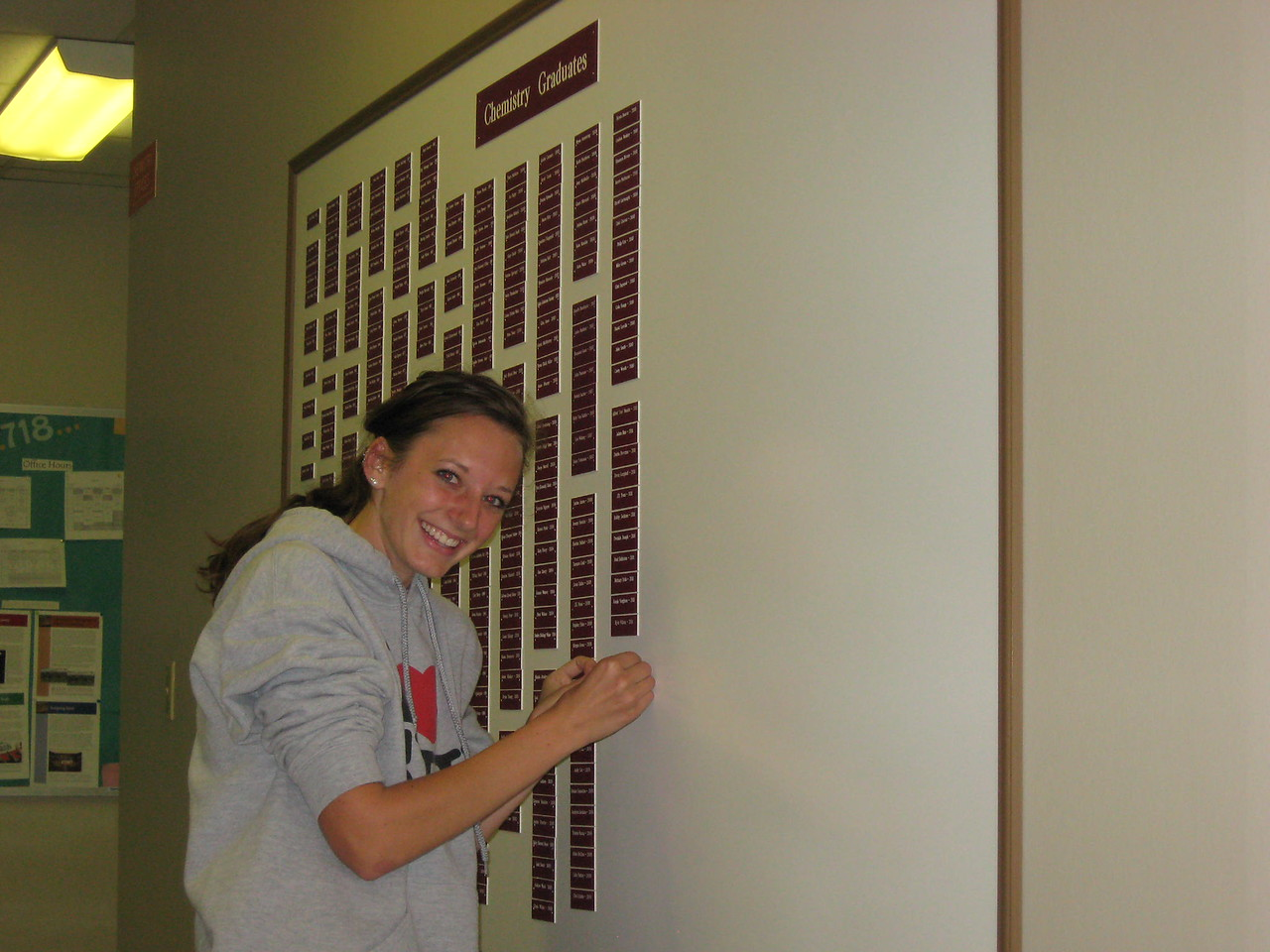 Chesney Burgweger putting her nameplate on the Chemistry Graduates board.