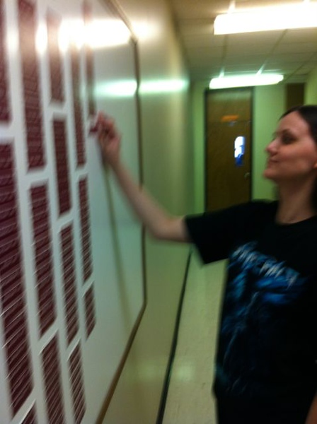 Cherokee Harding putting her nameplate on the Chemistry Graduates board.