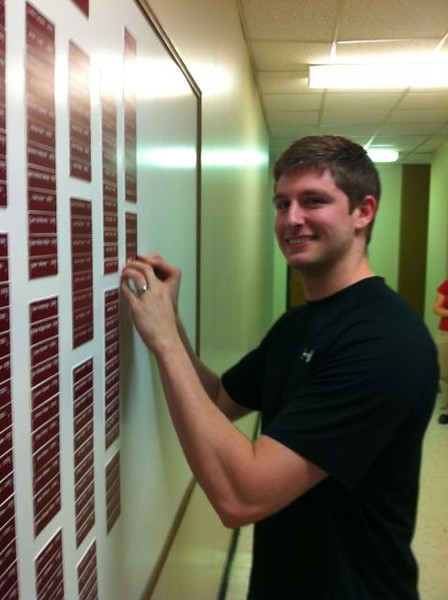 Ian Sanders putting his nameplate on the Chemistry Graduates board.
