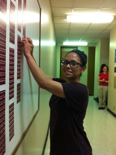 Elizabeth Valle putting her nameplate on the Chemistry Graduates board.