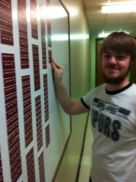 Kyle Roxby putting his nameplate on the Chemistry Graduates board.