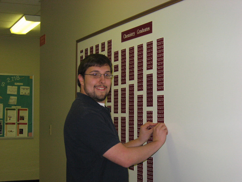 Brad putting his name on the Chem Graduates board.