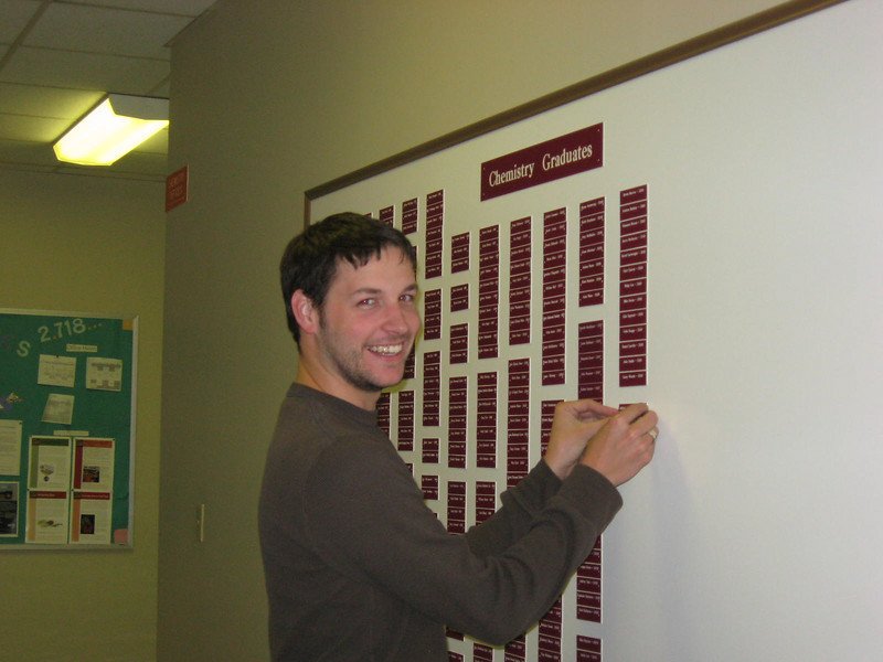 Trae putting his name on the Chem Graduates board.
