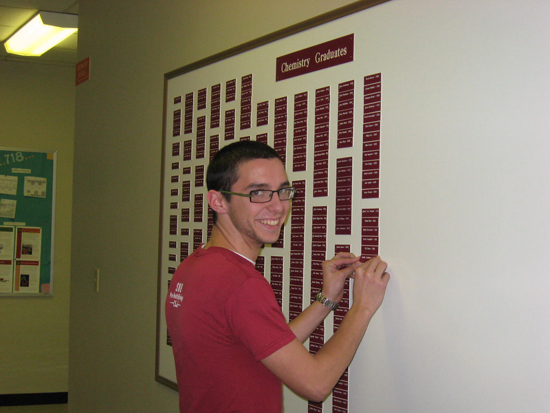 Robby putting his name on the Chem Graduates board.