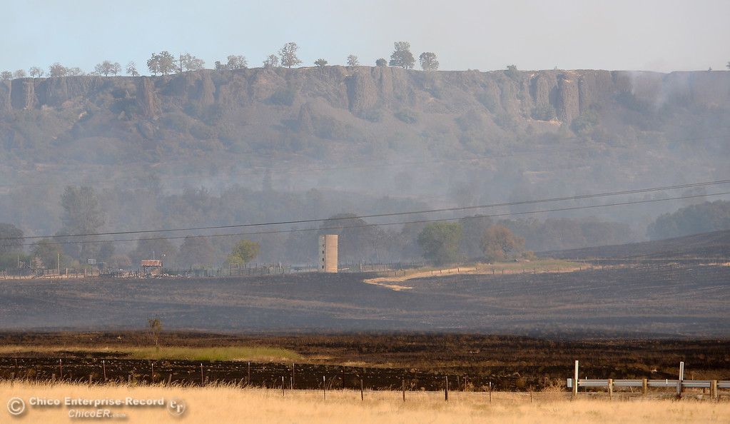 . Blackened grass is seen from Hwy. 70 looking toward Table Mountain as firefighters battle the Cherokee Fire Monday Oct. 9, 2017. (Bill Husa -- Enterprise-Record)