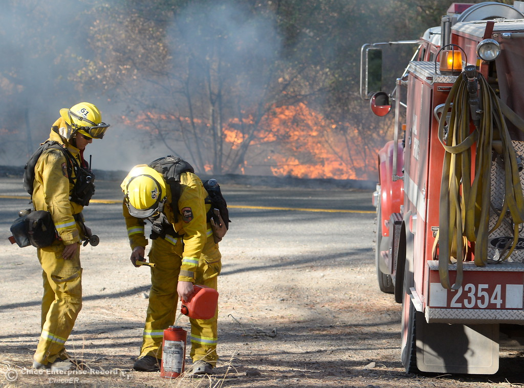 . Firefighters fill a drip torch with fuel to light a backburn to try and keep fire from crossing Cherokee Road below the Wildflower viewing area on the Oroville side Monday Oct. 9, 2017. (Bill Husa -- Enterprise-Record)