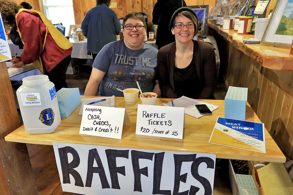 . The Lunenburg Lion\'s Club held a fundraiser for Cherry Hill Farm in Lunenburg on Saturday providing food, games, and music at Hollis Hills Farm in Fitchburg. Manning the raffle table at the fundraiser is Kate Nelson- kamau and Maureen Dupuis. SENTINEL & ENTERPRISE/JOHN LOVE