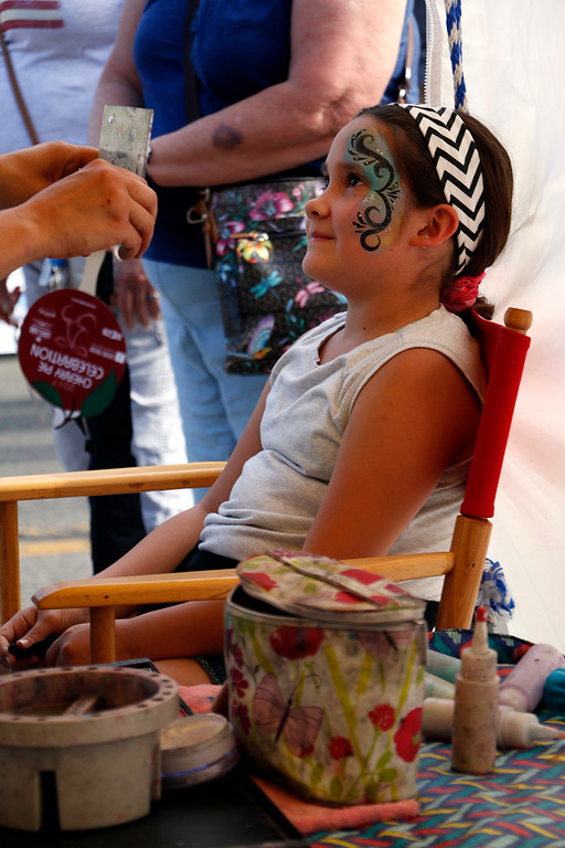 . Felicia Rodriguez, 10, admires her new face paint at the Cherry Pie Festival in Loveland on July 8, 2017. (Michelle Risinger/ Loveland Reporter-Herald)