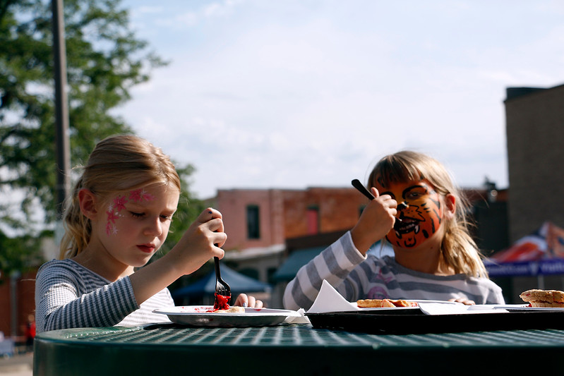 Ahna Barlow, 7 , right and Emily Michel, 7, left dig into pie and ice cream after getting their faces painted at the Cherry Pie Festival in Loveland on Saturday, July 8, 2017. (Michelle Risinger/ Loveland Reporter-Herald)