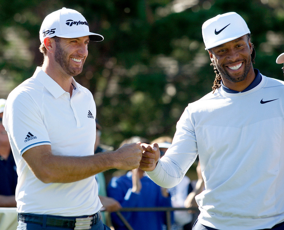 . PGA pro Dustin Johnson and Larry Fitzgerald from the Arizona Cardinals in the Chevron Shoot-Out at the Pebble Beach Golf Links practice green on Tuesday, Feb. 6, 2018.  The Chevron Shoot-Out is a two-person teams that faced off in a five-hole putting challenge for charity. Teams were made by pairing past tournament champions with champions from other sports.  (Vern Fisher - Monterey Herald)