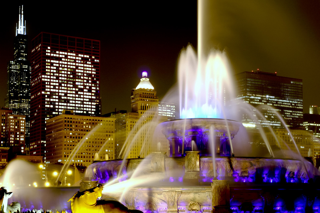 Buckingham Fountain, located in Chicago's Grant Park, has lighting that constantly changes colors.  This view, with the Sears Tower, CNA building, and others in the background, shows the rich blue lighting.
