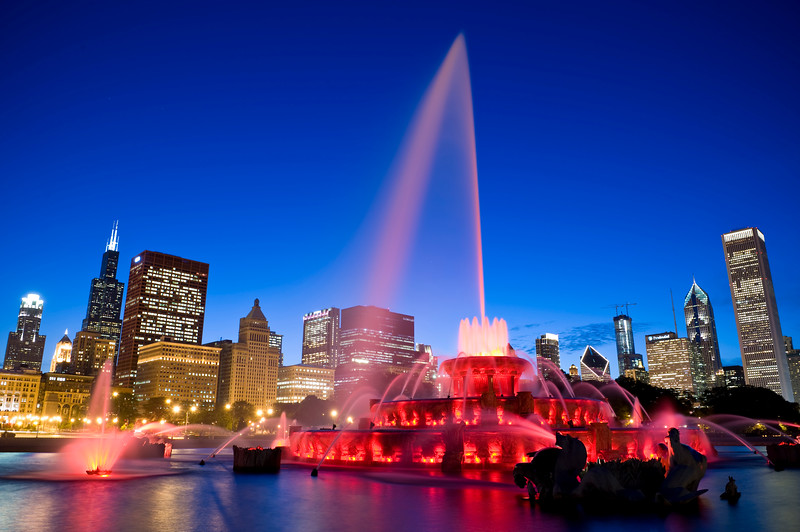 Buckingham Fountain glows as the sun sets behind Chicago's skyline.