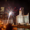 Fireworks over the Chicago River at night over the North Michigan Avenue bridge as part of the winter fireworks spectacular celebration with Wrigley Building illuminated