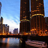 A tour boat approaches the Michigan Avenue Bridge and Marina City on the Chicago River, at night.