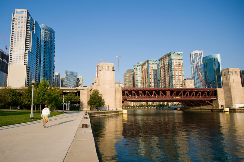 Chicago River Walk, the  riverwalk starts with Lake Point Tower and green trees.
