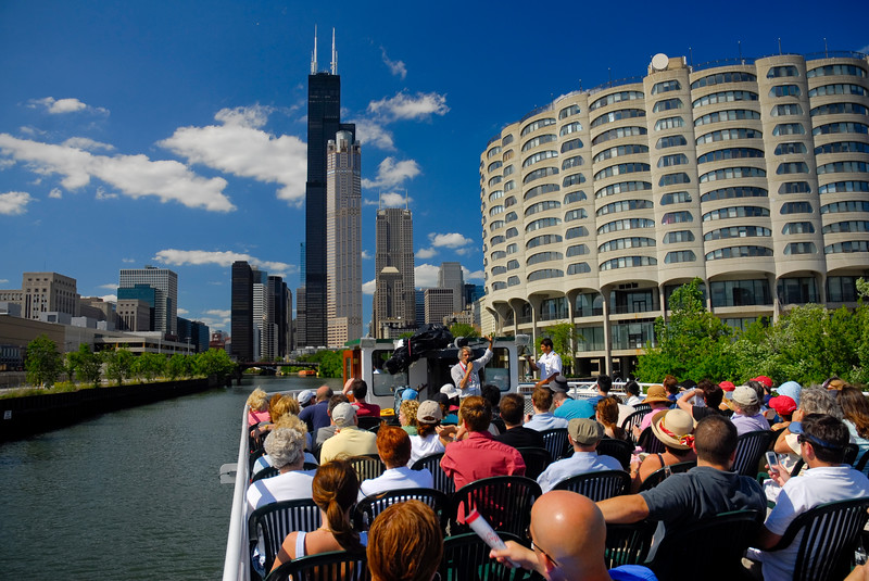 Sightseers take part of a river tour with Downtown Chicago in the background