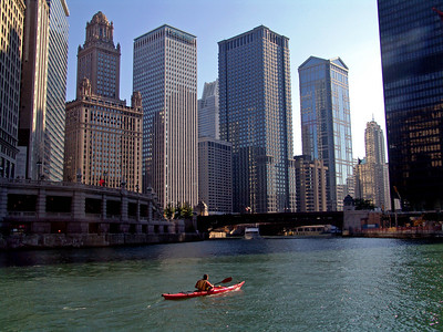 Man kayaking in the Chicaogo River, construction on Trump Tower just beginning (right hand center)