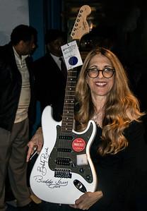 Publicist Lynn Orman shows the guitar being raffled during the Bob Fioretti Fundraiser