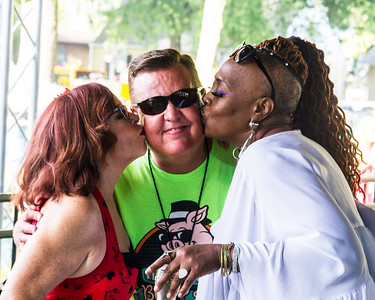Liz Mandeville (l) and Ms. Trish (r) plant a kiss on one of the WLTH radio staff members
