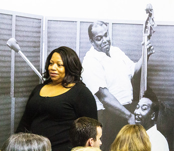Jackie Dixon standing in front of a photo of her famous dad, Willie, with Muddy Waters.