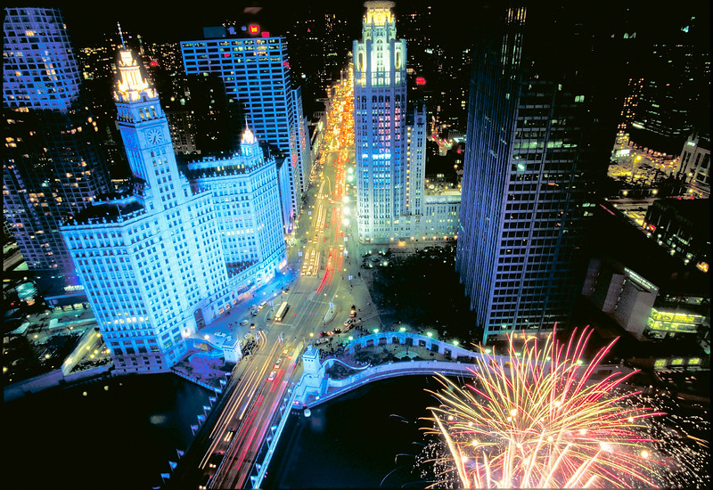 North Michigan Avenue is aglow at night with fireworks in the foreground.
