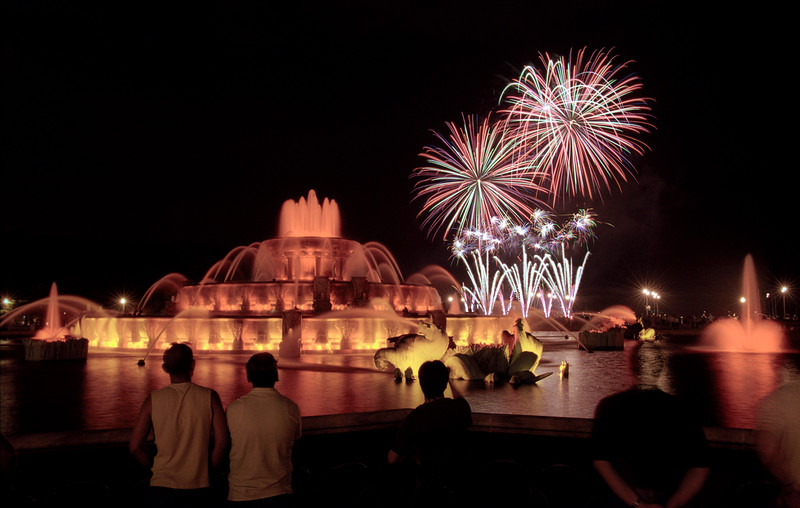 Tourist enjoy the fireworks dispaly on the lakefront with Buckingham fountain in the foreground.