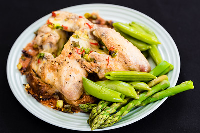 Chicken wings on fried bread with sugar snap peas and asparagus