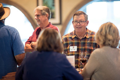 Tom Roth (center) enjoys a conversation with fellow guests at the Chico Chapter Fall Mixer at Almendra Winery on Saturday, October 14, 2017 in Chico, Calif.  (Jessica Bartlett/University Photographer)