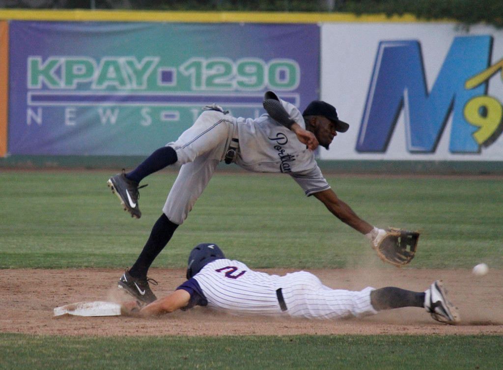 . Chico Heat\'s Jake Davison dives into second to bet Portland Pickles\'s Kelechi Anyanwu to the bag during the home opener against the Portland Pickles May 30, 2017 at Nettleton Stadium in Chico, California. (Emily Bertolino -- Enterprise-Record)