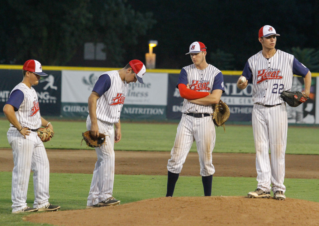 . Chico Heat\'s Brandon De La Guardia, Mark Jones and Bailey Zimmer, left to right, stand behind incoming pitcher Tanner Clark (22) as he practices his throw during a game against the Marysville Gold Sox on the third night of a three game series Saturday August 5, 2017 at Nettleton Stadium in Chico, California. (Emily Bertolino -- Enterprise- Record)