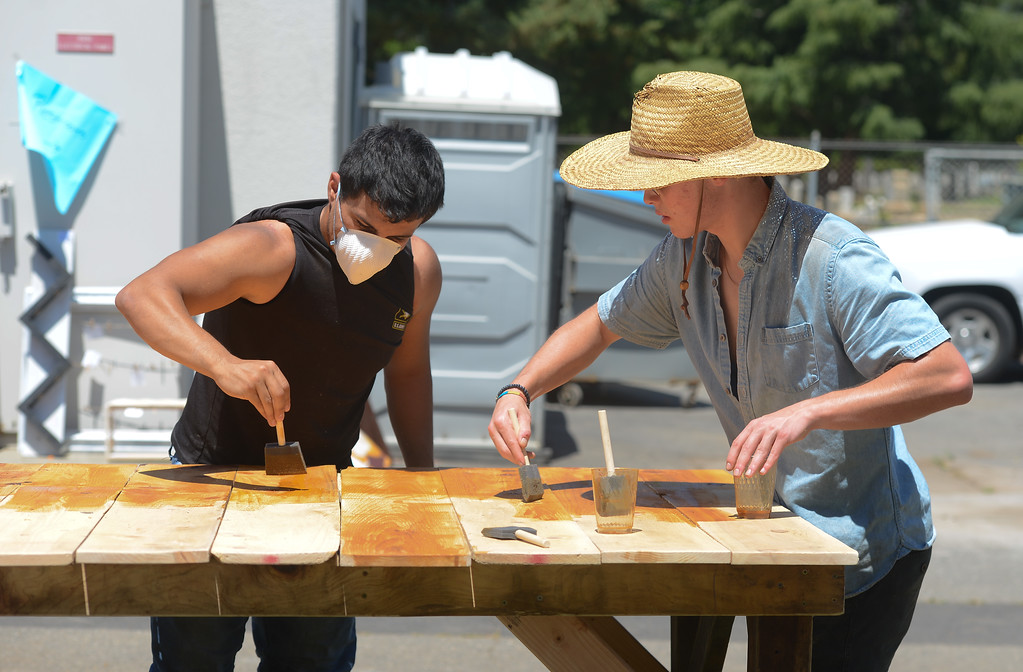 . Spencer Christiansen and Rafael Orozco stain a wood table, May 18, 2018,  in Chico, California. (Carin Dorghalli -- Enterprise-Record)