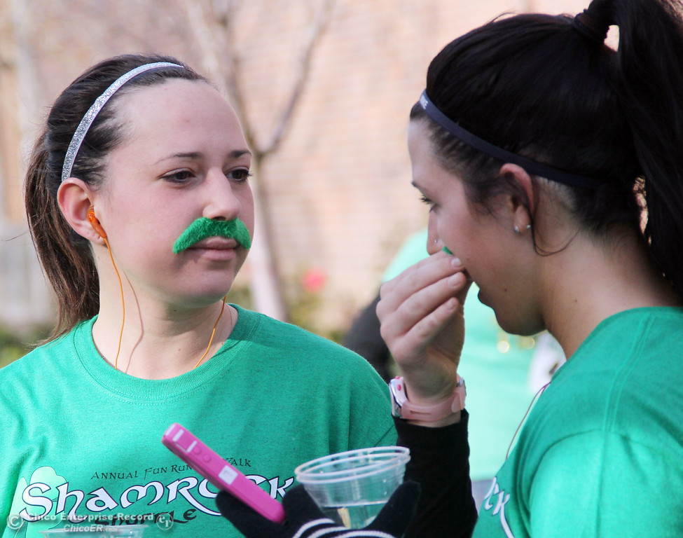 . Sierra Owens (left) watches Emily Flesher (right) adjust her green mustache as people took part a run and pancake feed in the 11th Annual Shamrock Shuffle for St. Patrick\'s Day festivities on the Chico State campus Saturday, March 17, 2012 in Chico, Calif. 