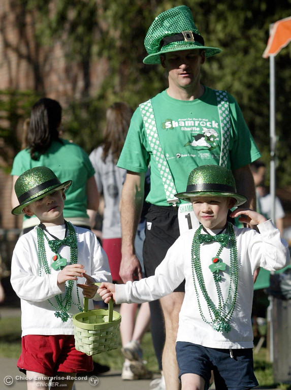 . Sean Farrell (top) walks behind his twin boys, Riley Farrell, 6 (left) and Bretten Farrell, 6 (right) as they pass out chocolate coins to people at the Shamrock Shuffle on the CSUC campus for St. Patrick\'s Day on Saturday, March 17, 2007 in Chico, CA. 