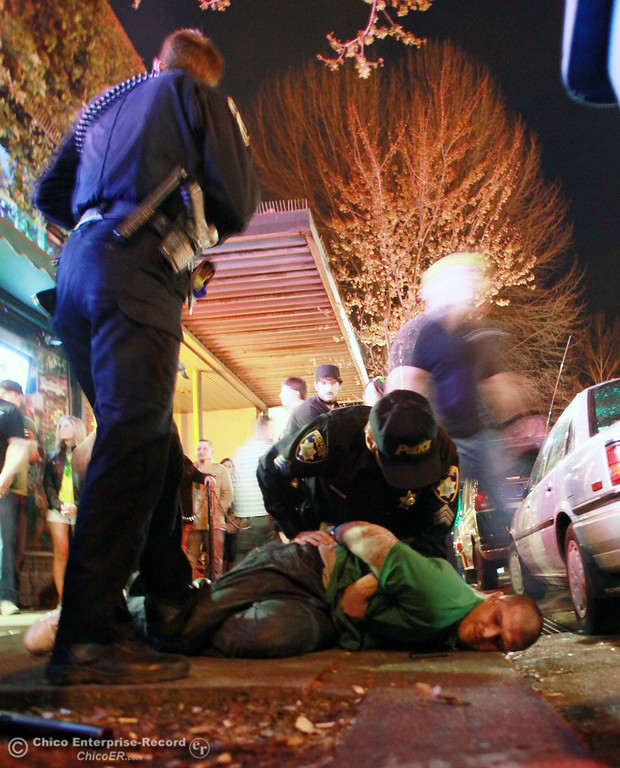 . Paradise Police officer Robert Wright (left) and Sgt. Steve Roe arrest a male individual who was caught fighting at LaSalles as people hit the town for something to celebrate during St. Patrick\'s Day Saturday, March 17, 2012 in downtown Chico, Calif. Chico Police were called in for backup to assist in detaining the suspect who was kicking, screaming and being unruly to law enforcement. Paradise Police were assisting with DUI checks as part of the AVOID Grant through the Office of Traffic Safety.