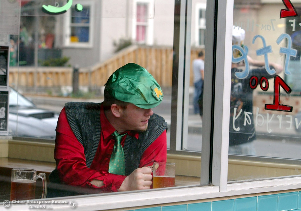 . A man peers from Five & Eye resturaunt at chicoans that take to the streets of Downtown Chico near 5th St. and Ivy St. for St. Patrick\'s Day celebrations Tuesday, March 17, 2009 in Chico, CA. 
