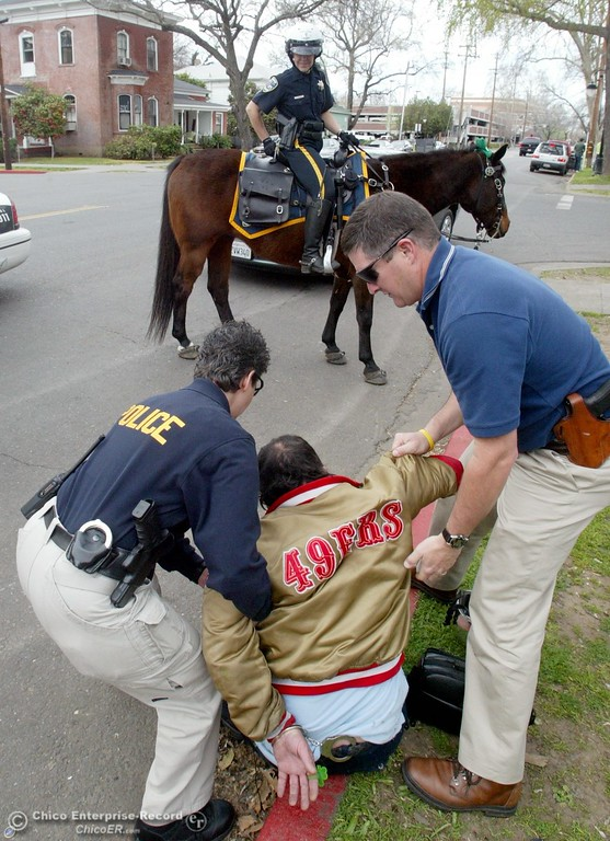 . March 17 2009 in Chico Ca. Downtown Saint Patricks Day. In this picture,.Arrested at 3rd and Ivy for being drunk in public and on parol is Ricky Dunn. Chico Police Lori Klingerman and Ford Porter take him in custdy as Officer Abby Madden on her horse \'Magic\' look on.,(Ty Barbour/Chico Enterprise-Record)