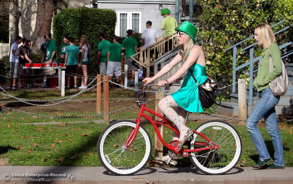 ". Kaitlynn ""KB\"" Wolfe, 21 (left) rides her bike with Sarah Peters, 23 (right) as they head towards a house along W. 4th St. near Ivy St. as St. Patrick Day celebrations spill into the streets as partiers, CSUC/Butte students and non-students, enjoy the week off on Wednesday, March 17, 2010 in Downtown Chico, Calif. 